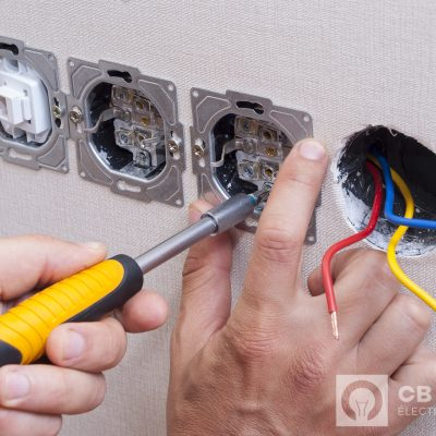 electrician connects the sockets to the electrical wires on the wall